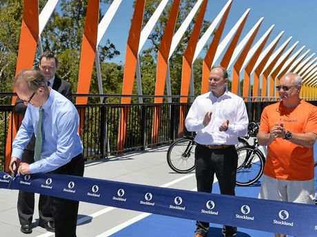 Division one councillor Rick Baberowski cuts the ribbon to open the new Aura Boulevard Bridge, watched by Stockland regional manager Ben Simpson, project director Adrian Allen, and Les Thomas from the Bellvista Community Association.