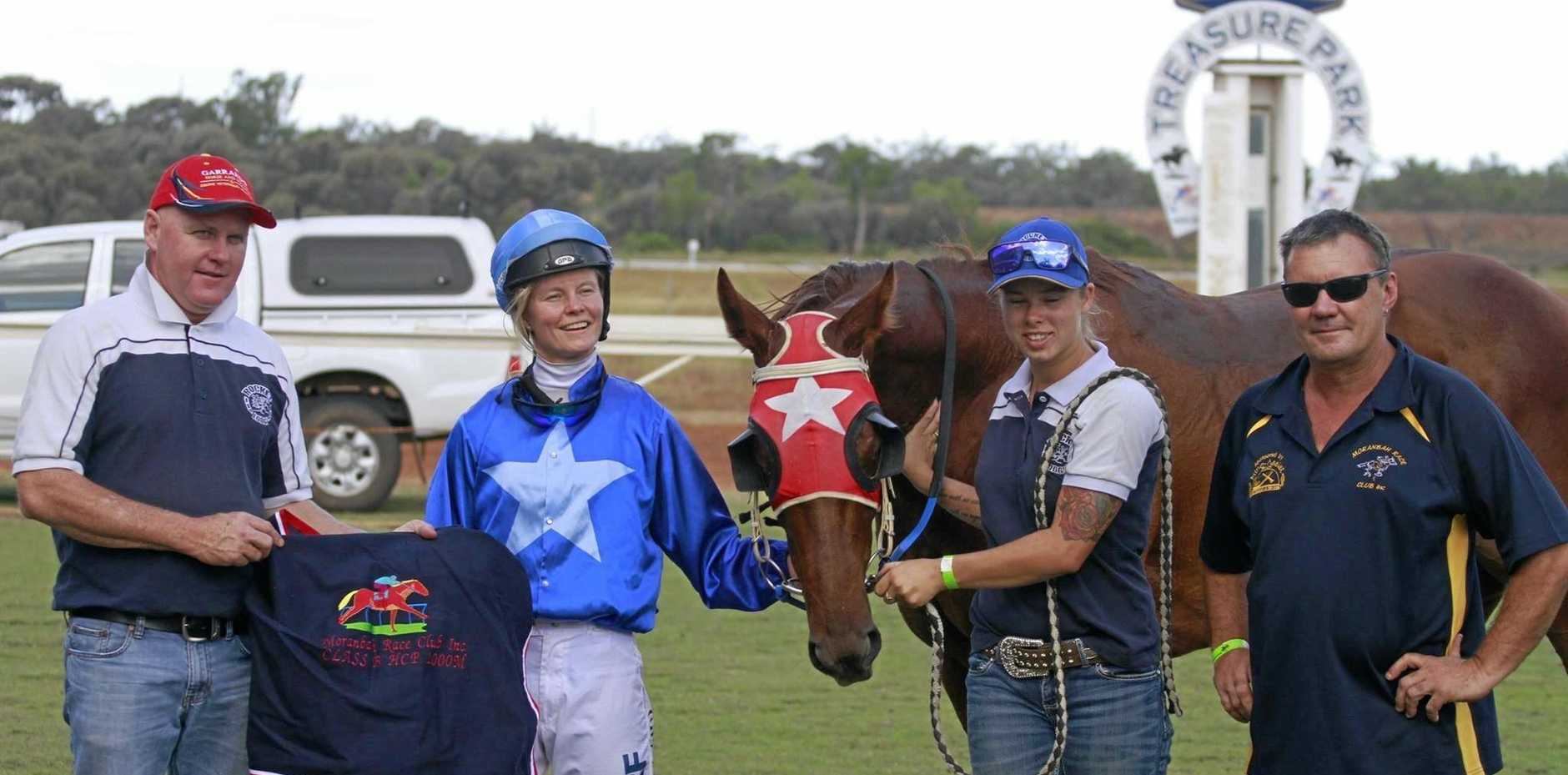 NUMBER ONE: John Manzelmann in the winners' circle with Moranbah president Brent Sparks and connections at Treasure Park.
