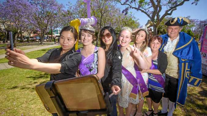 Elly Lee (front) and Helen yin (third from left) of Sydney - get in a quick photo with the Jacaranda Queens Party (from left) Sharni Wren, Heidi Madsen, Shannon Carter, Carol Smith and town crier Trevor Green at the daily Jacaranda Meet and Greet.