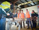 Apprentice Baylee Rigby demonstrates correct grinding technique for senator Chris Katter, Zac Beers and Bill Shorten mp when they visited GAGAL yesterday. Other apprentices watching on are Jarrod Pengelly, Luke Ropmagnolo and Zoe Jackson.