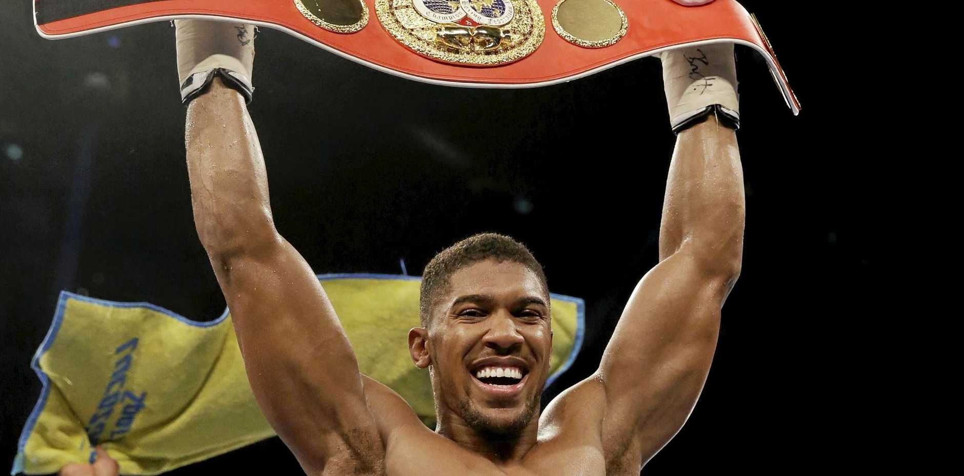 British boxer Anthony Joshua holds up his belt after defeating US boxer Dominic Breazeale in their IBF heavyweight title bout at the O2 Arena in London in June.