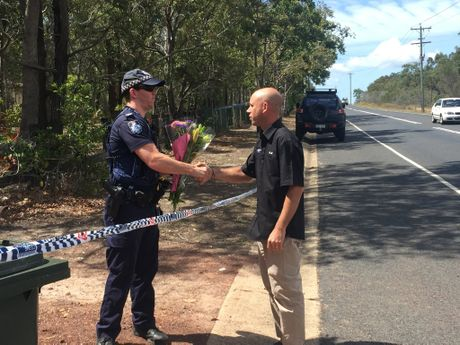 IN MEMORY: A member of the public asks a police officer to add his bouquet of flowers to the others at the scene of a fatal shooting in Booral.