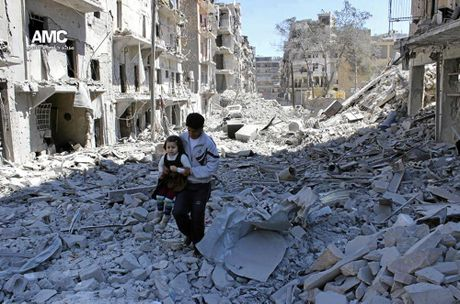 A Syrian man holding a girl as he stands on the rubble of houses destroyed by Syrian government forces air strikes in Aleppo, Syria.