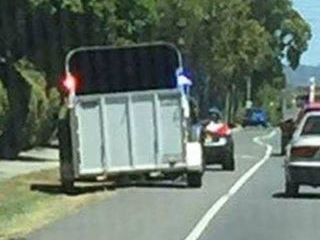 The unmarked police vehicle towing a horse float.