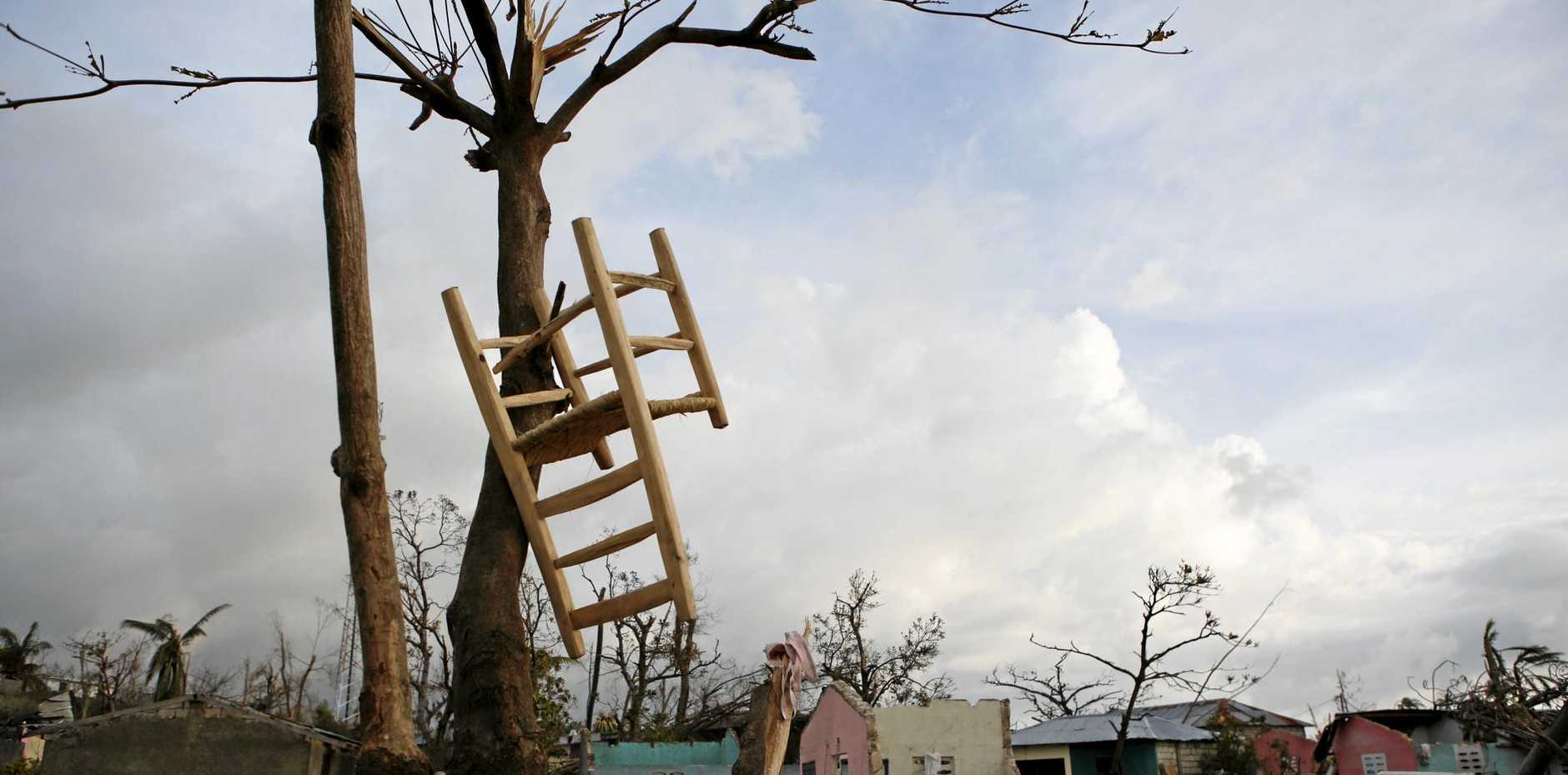 A salvaged chair hangs in a tree amidst nearby homes destroyed by Hurricane Matthew, in a seaside fishing neighborhood of Port Salut, Haiti, Sunday, Oct. 9, 2016. Nearly a week after the storm smashed into southwestern Haiti, some communities along the southern coast have yet to receive any assistance, leaving residents who have lost their homes and virtually all of their belongings struggling to find shelter and potable water .(AP Photo/Rebecca Blackwell)