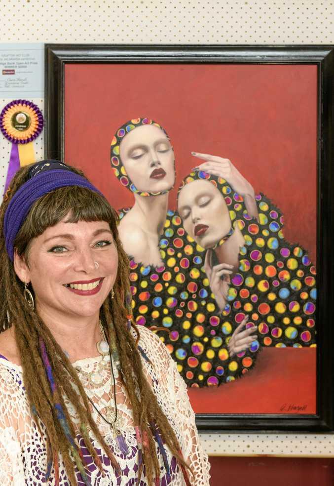 RAINBOW COLOURS: Chris Hazell in front of her Bendigo Bank Art Prize winning work at the Grafton Art Club's Jacaranda show.