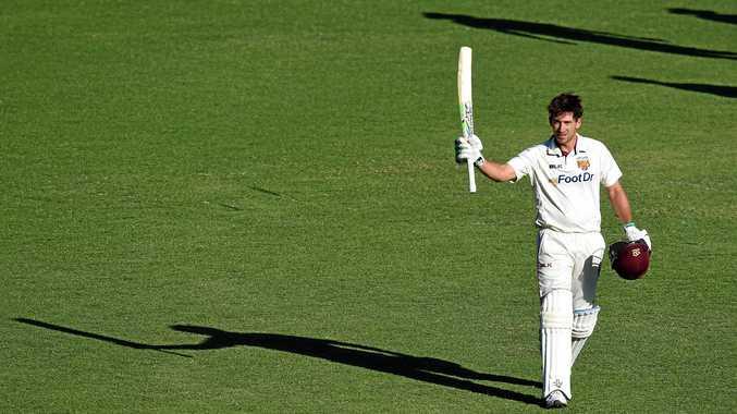 Queensland batsman Joe Burns raises his bat after scoring a Sheffield Shield century against New South Wales at the Gabba last month.