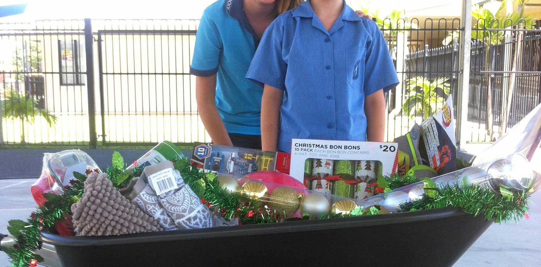 Grace Druery and Isy Macey showing the Christmas Hamper and grocery bags up for grabs at the Fair.