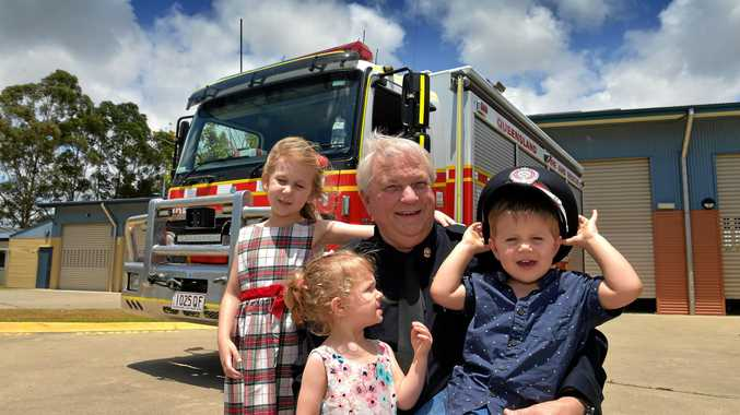 Caloundra auxiliary firefighter Lieutenant Russell Weir embraces his grandchildren Sarannah, Arabelle and Maxwell Leary after receiving his National Service Medal First Clasp.