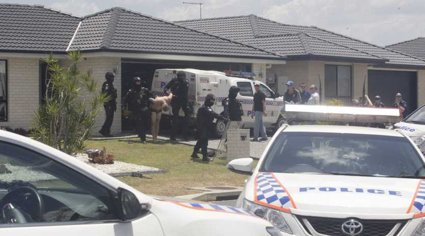 CABOOLTURE SIEGE: Police dragging a man out of the Caboolture home where he had barricaded himself since early this morning.