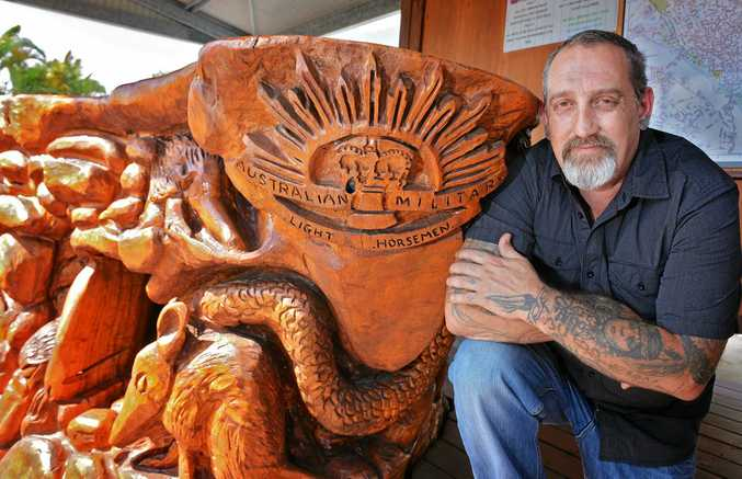 REMEMBRANCE GIFT: Chainsaw carver Ken Magri with his Australian Military statue at the Gympie caravan park.