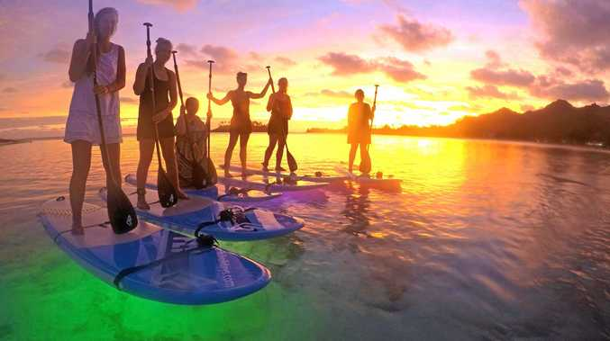 Night-time stand-up paddling with LED lights under the board is one of many activities for visitors to the Cook Islands and, right, women show off their bright floral headbands.