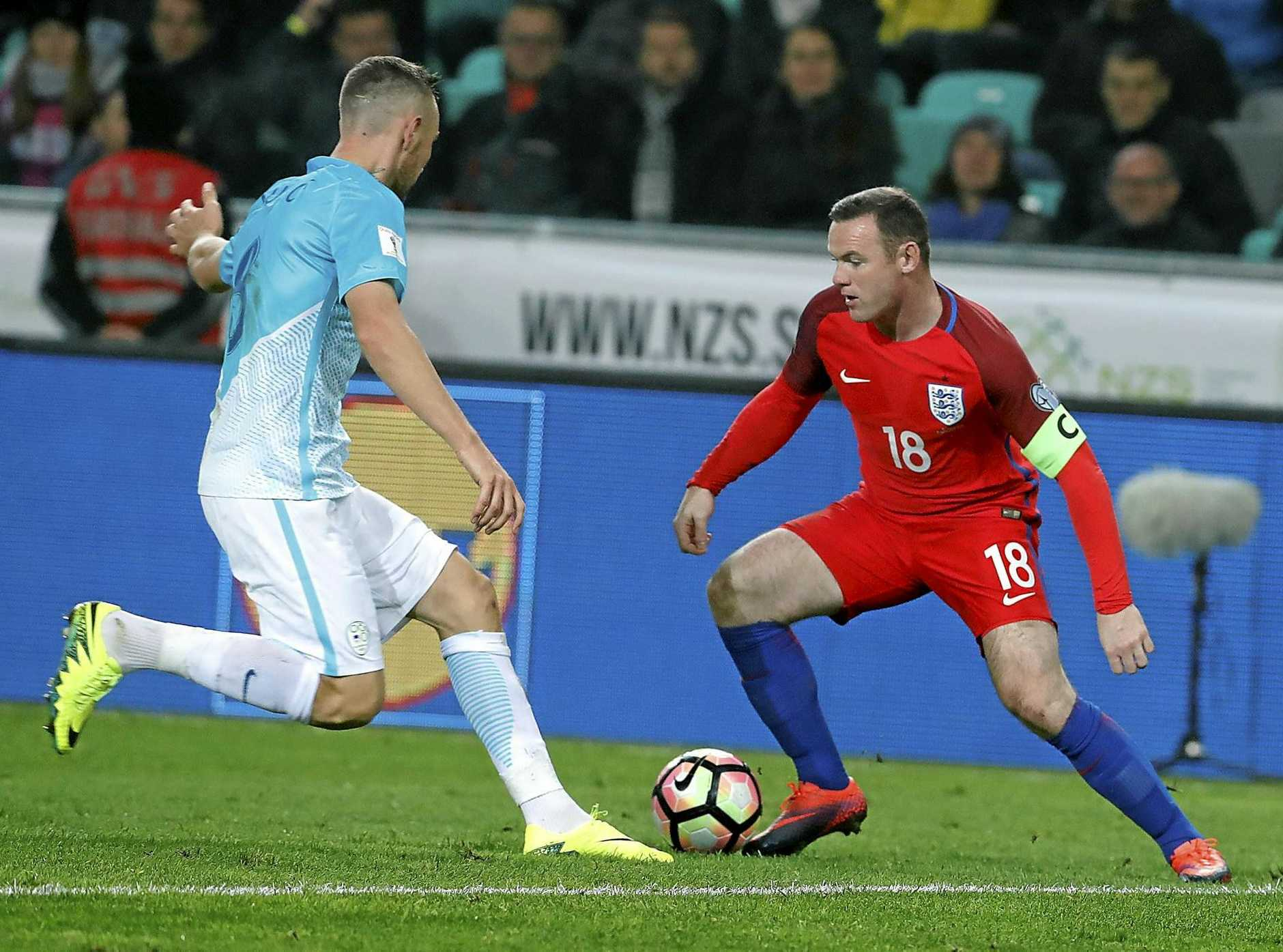 England's Wayne Rooney (right) in action against Slovenia's Benjamin Verbic in Ljubljana.