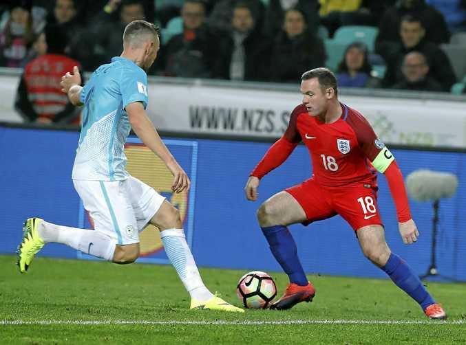 England's Wayne Rooney (right) in action against Slovenia's Benjamin Verbic in Ljubljana.