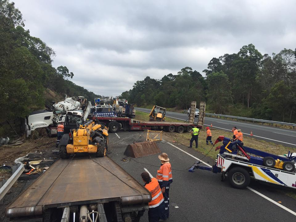 'It's a bit of a mess': Tow truck drivers work to clear the wreckage of a semi-trailer that has blocked the Bruce Hwy near Nambour.