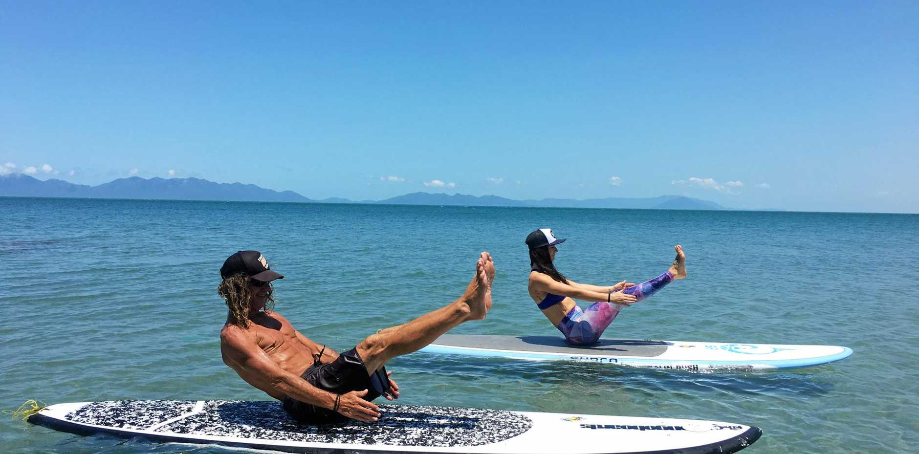 BALANCING ACT: Mark Bailey and Chloe Santarossa practise Stand Up Paddle Board yoga, which Chloe is now offering classes in at Bowen beaches.