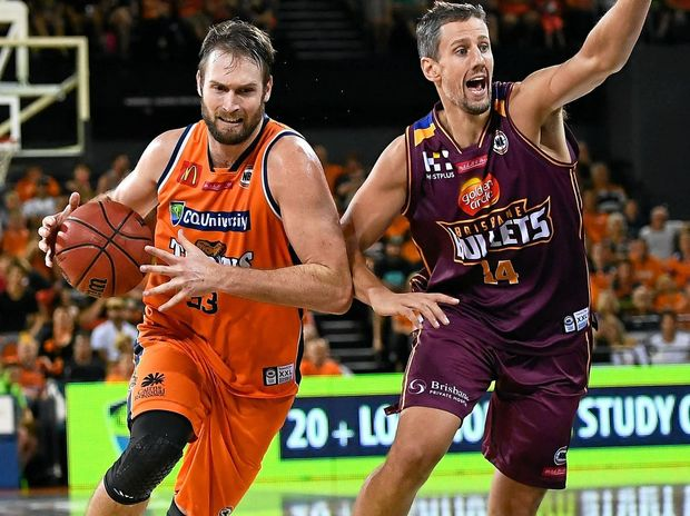 Mark Worthington of the Taipans drives to the basket past Daniel Kickert of the Bullets.