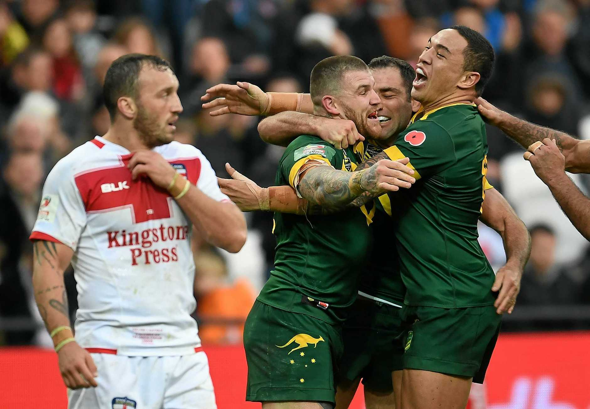 Josh Dugan celebrates with Australian teammates after scoring a try against England.