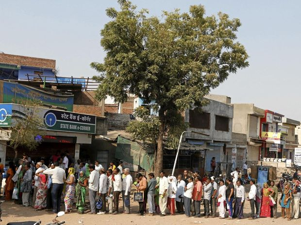 Indians stand in a queue to deposit and exchange discontinued currency notes outside a bank in Ahmadabad.