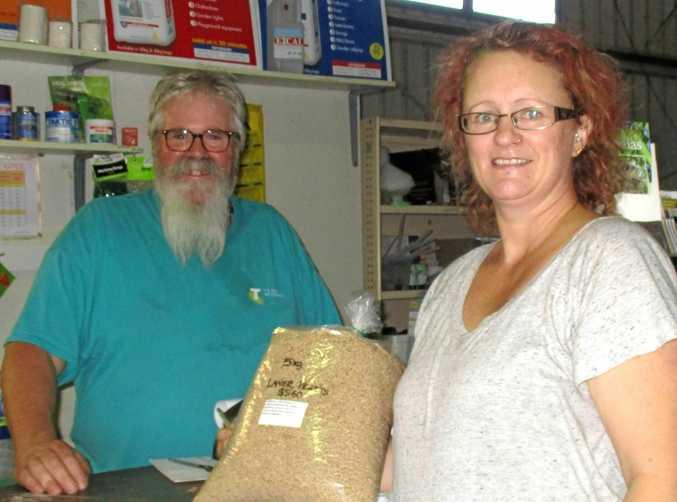 NEW ERA BEGINS: Warren Francis serves his first customer, Lydia Penfold, at Widgee Rural.
