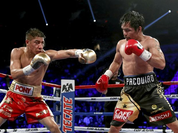 American Jessie Vargas and Manny Pacquiao, of the Philippines, trade blows during their WBO welterweight title boxing match.