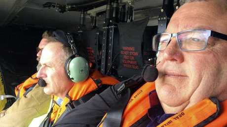 New Zealand Prime Minister John Key, centre, and acting Civil Defense Minister Gerry Brownlee, right, fly over Kaikoura, New Zealand, to inspect the damage following a powerful earthquake on Monday
