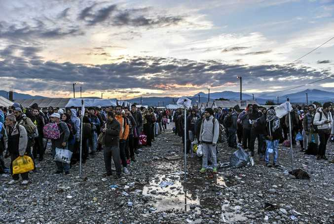 Migrants and refugees wait to board a train near Gevgelija in southern Macedonia after crossing the Greek-Macedonian border on September 27, 2015. Macedonia is a key transit country in the Balkans migration route into the EU, with thousands of asylum seekers and migrants -- many of them from Syria, Afghanistan, Iraq and Somalia -- entering the country every day. AFP PHOTO / ARMEND NIMANI