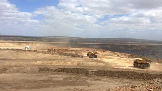 An excavator and haul trucks at BHP Billiton Mitsubishi Alliance's Daunia mine in Central Queensland.