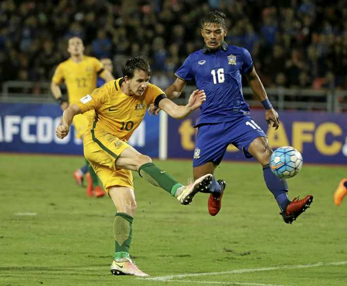 Robbie Kruse of Australia and Pratum Chuthong of Thailand battle for the ball.
