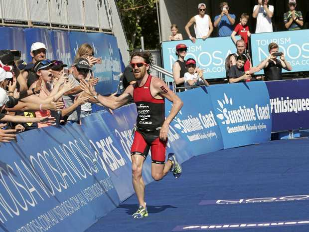 Dan Wilson high fives the crowd to win the Noosa Triathalon.