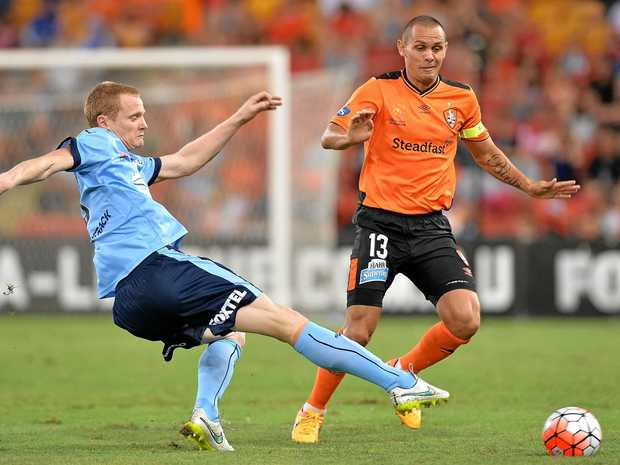 Jade North of the Roar and Matthew Simon of Sydney FC challenge for the ball.
