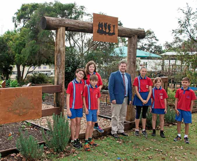 REMEMBERING: (from left) Jarrah Jones, Tyleigh Cottom, Soli Dewhirst-McDonald, Jess Thompson, Gracie Robb, and Oliver Stephens show Llew O'Brien (centre) around the garden. INSET: Llew O'Brien speaking to the students while Tyleigh Cottom and Jess Thompson hold up the Australian Flag.