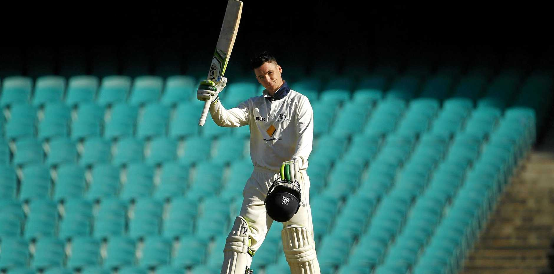 Victorian batsman Peter Handscomb raises his bat after scoring a century against New South Wales at the Sydney Cricket Ground.