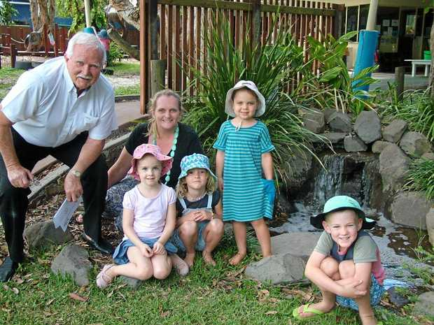 WATER WISE: Ian McDonald of Noosa Heads SLSC supporters club checks out the water feature with  Caitlyn, Maggie, Asha and Toby and kindy co-director Lisa Stanley.