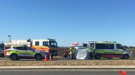 Paramedics treating a man seriously hurt in a crash between a car and truck in the Lockyer Valley.