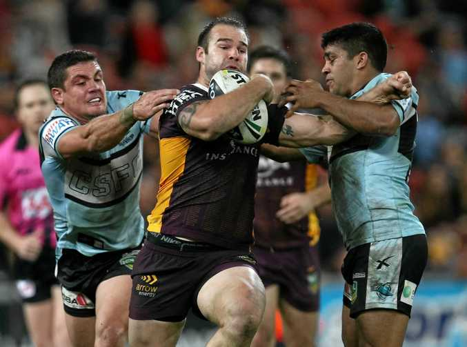 Scott Anderson charges through Chris Heighington and Tyrone Peachey during the Round 18 NRL match between the Brisbane Broncos and the Cronulla Sharks at Suncorp Stadium in Brisbane, Friday, July 12, 2013. (AAP Image/Action Photographics, Colin Whelan) NO ARCHIVING, EDITORIAL USE ONLY