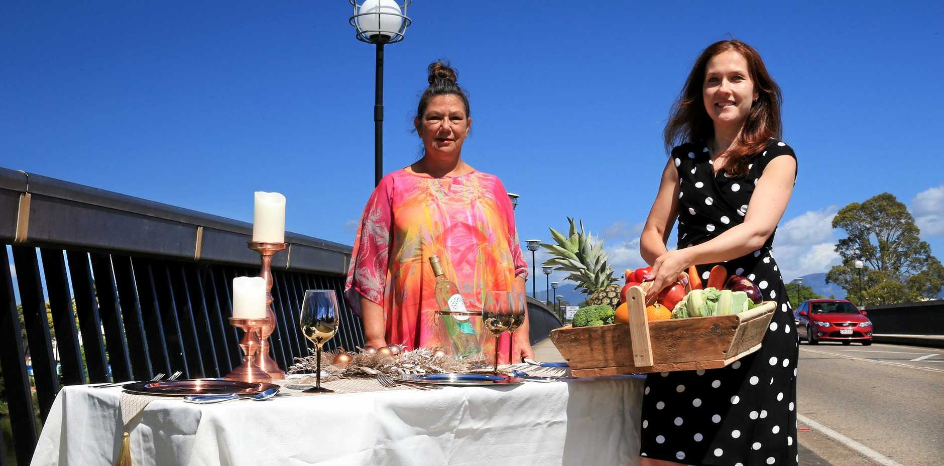 GOOD TIMES: Kerry Turner and Katya Simmons get into the swing of things setting up a table on the Murwillumbah Bridge ahead of the Tweed Foodie Fest on December 3.