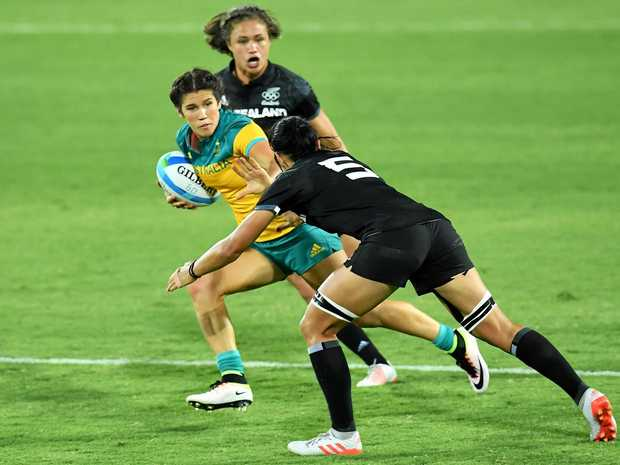 Australia's Charlotte Caslick tries to fend off a tackle by Sarah Goss of New Zealand in the women's rugby sevens at the Rio Olympics.