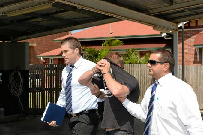 Mackay detectives lead a Middlemount man into the police station to face charges of the murder of a woman who fell from a ute on Dec 31.12.14. Photo Lee Constable / Daily Mercury