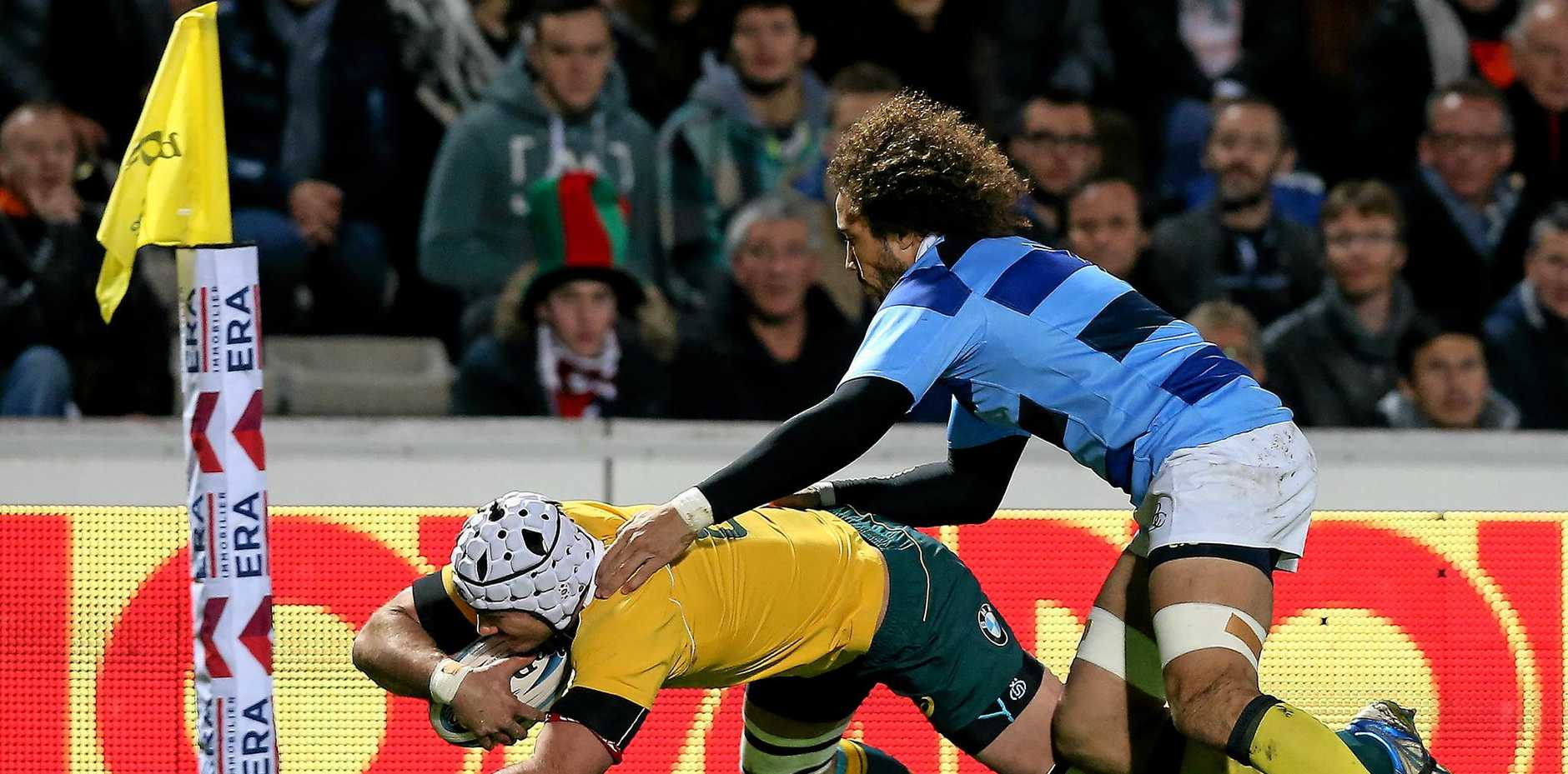 Ben Mowen of Australia scores a try against the French Barbarians in Bordeaux.