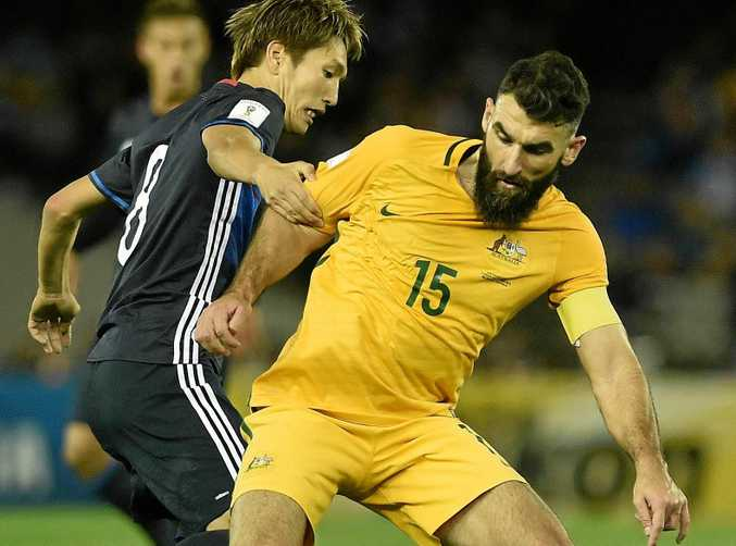 Genki Haraguchi of Japan (left) and Mile Jedinak of Australia fight for the ball.