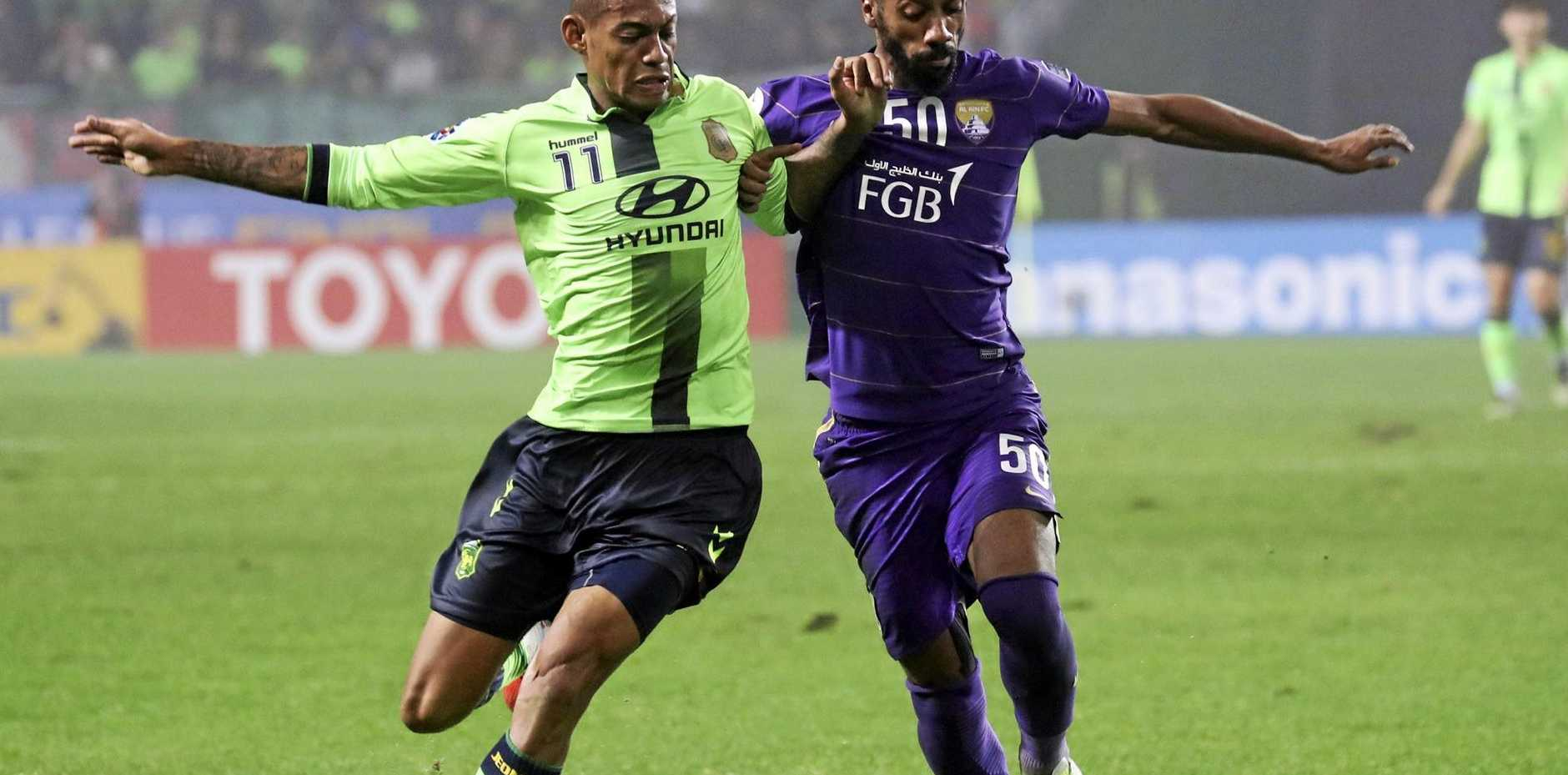 Ricardo Lopes (left) of Jeonbuk Motors fights for the ball with Mohammed Fayez of Al Ain.