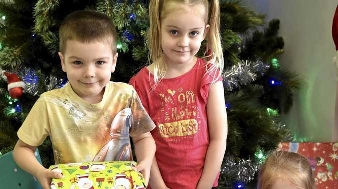 THE GIVING TREE: Eastwood Early Education Centre children (from left) Fletcher Turner, Kaitlyn Reeves and Ivy Luthor show off some of the presents donated for the appeal.
