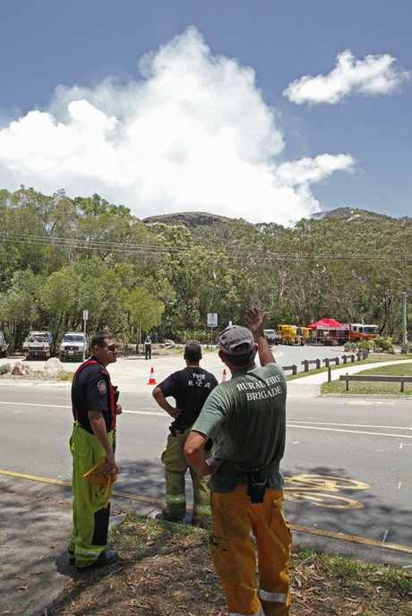 Firefighters watch on as smoke rises from a vegetation fire on Mount Coolum.