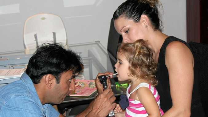 Dr Sheraz Dost treating Kaliyah Shirvington, 2, while she sits on her mother, Leilani Cooper-Shirvington's lap.