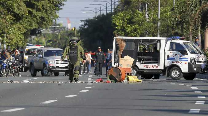 BOMB SCARE: A  bomb   squad member   after detonating   a  suspicious package  Manila.