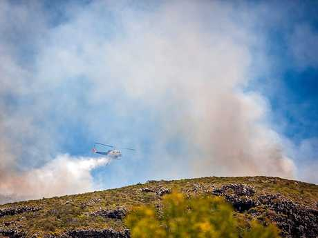 Helicopters water bomb a blaze burning on Mount Coolum.
