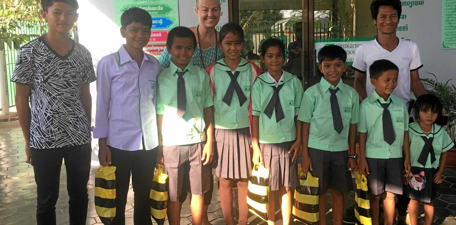MIGHTY EFFORT: Trish Simpson with some of the Cambodian children and families she is helping with her Happy Hub.