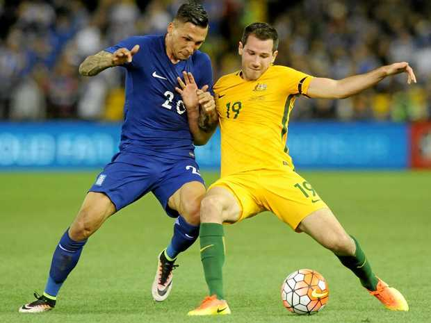Ryan McGowan of the Socceroos and Jos Holebas of Greece fight for the ball during their friendly in June.