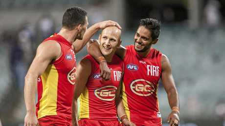 Gary Ablett celebrates a Suns win with Steven May (left) and Aaron Hall.